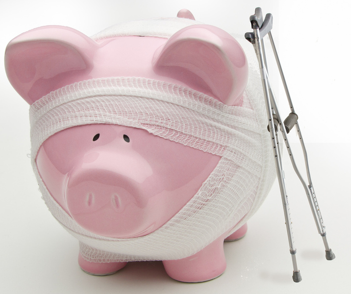 A piggy bank wrapped in bandages with a set of crutches.