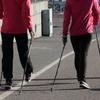 A couple using Nordic walking poles on a city sidewalk. Photo credit Tsippendale on Pixabay.